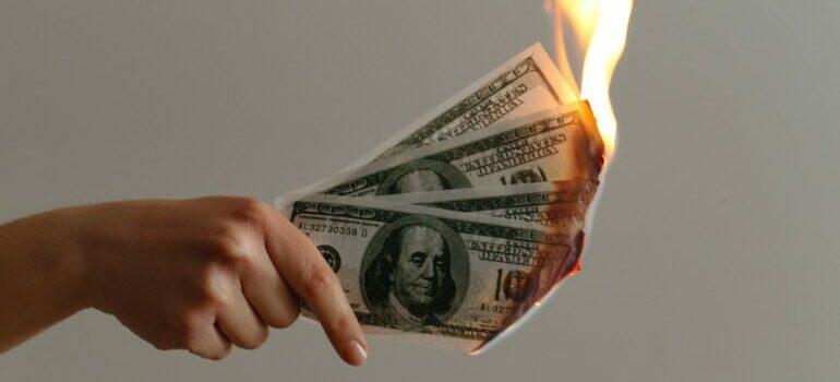 A person holding burning dollar bills.