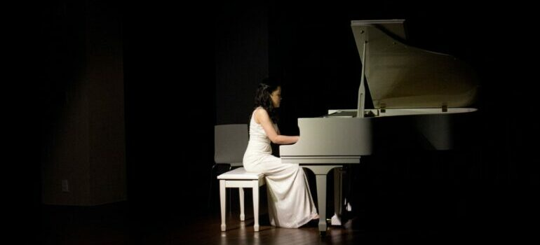 Woman in white dress playing the piano after the relocation with piano movers Austin.