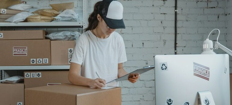 female with a hat working, moving boxes on the table and behind