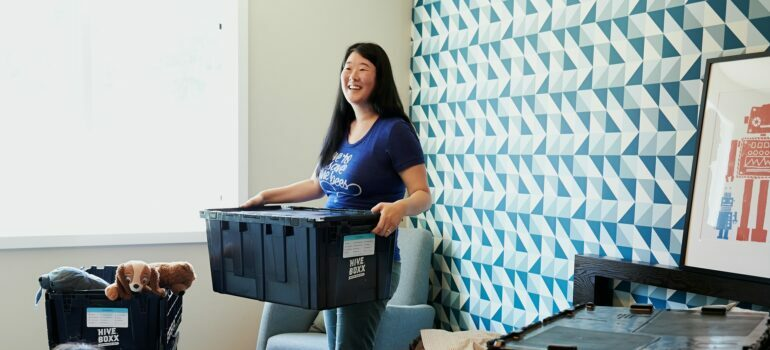 Woman in blue shirt holding packing box
