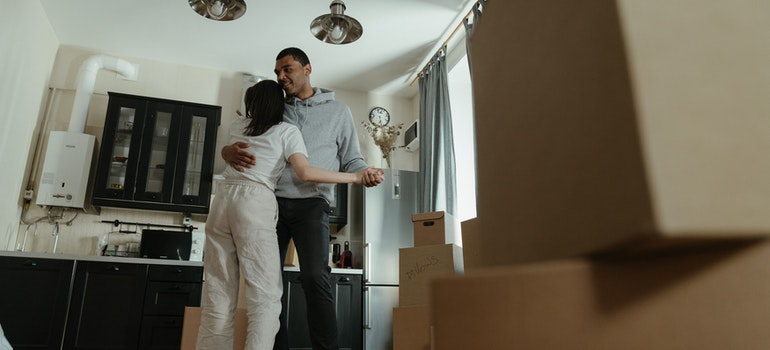 A couple dancing next to moving boxes
