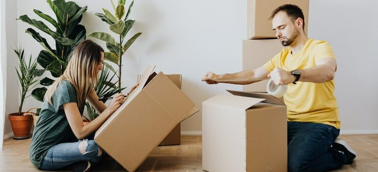 man and woman sitting on the floor and packing boxes