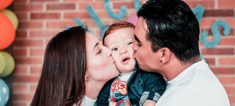a couple kissing their toddler on the cheeks at the same time