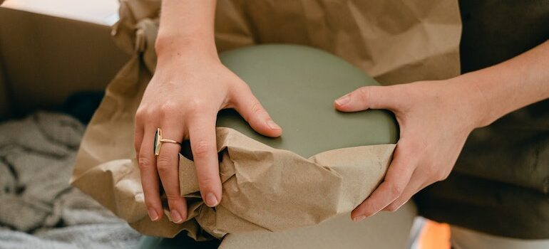 hands wrapping with paper a bowl