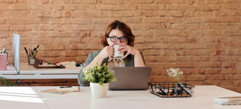 woman sitting in front of the laptop, thinking, drinking coffee