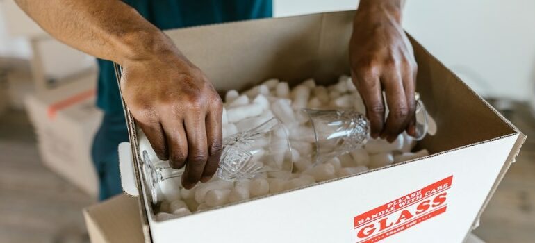 professionals packing glassware in the cardboard box filled with packing peanuts