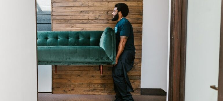 person carrying green sofa