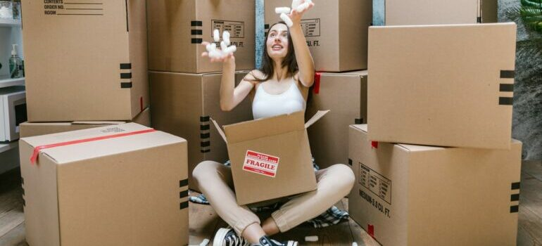 A woman in a storage unit surrounded by moving boxes