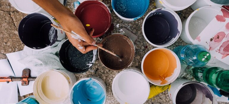 a lot of buckets with paints and a hand holding a brush