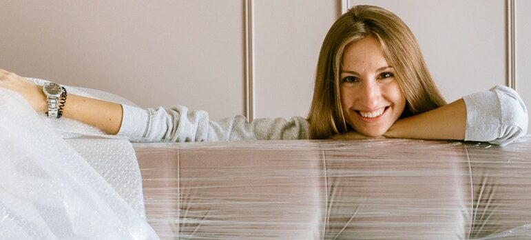 a woman sitting behind a couch covered in plastic wrap