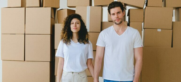 a man and woman in front of cardboard boxes