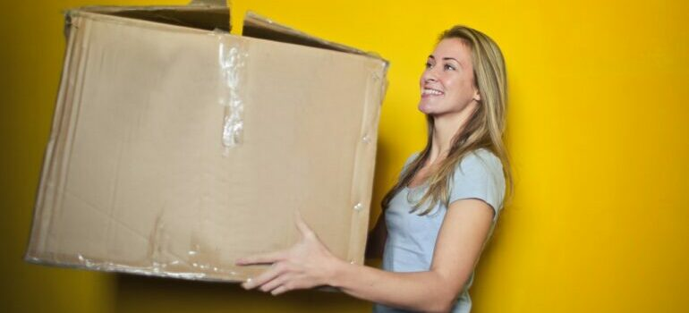a young woman carrying used moving box