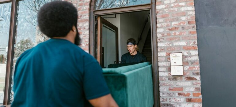 two movers carrying a couch outside of the house