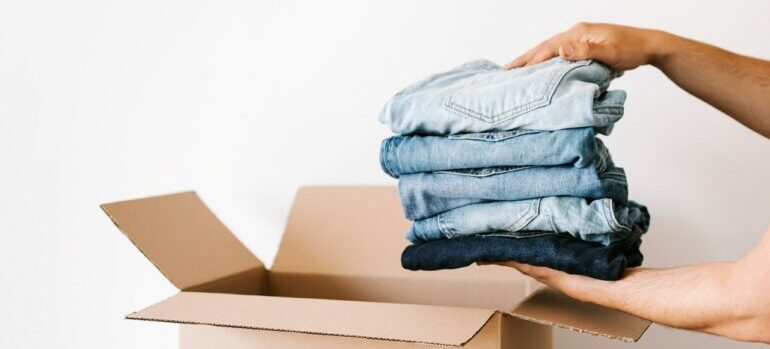person putting folded clothes in a box
